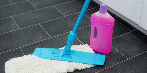 Wischmob und Putzzeug stehen auf dem Boden als Symbol für Wischen und sauberen Boden